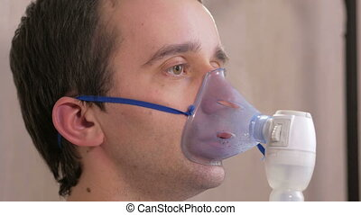 Young man holding a mask from an inhaler at home. Treats ...