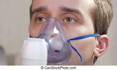 Young man holding a mask from an inhaler at home. Treats...