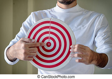 young man holding a red dartboard