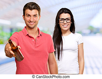 Young Man Holding Alcoholic Bottle In Front Of Happy Woman