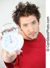 Young man holding an alarm clock