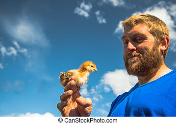 Young man holding baby chick