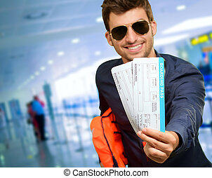 Young Man Holding Boarding Pass, indoor