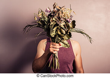 A sad young man is holding abouquet of dead and withered flowers