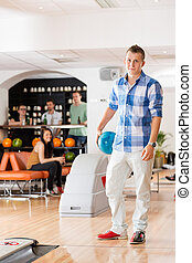 Young Man Holding Bowling Ball in Club