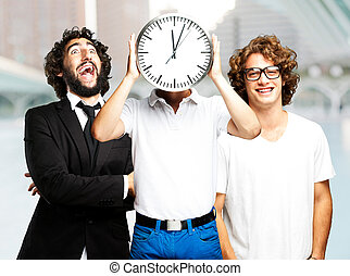 young man holding clock with friends at city