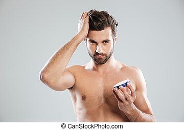 Young man holding cream isolated