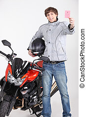 Young man holding driving license stood next to motorcycle