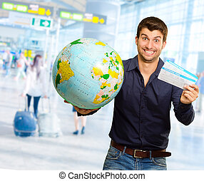 Young Man Holding Globe And Boarding Pass, Indoor