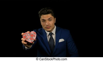 Young man holding heart shaped cardboard box with red heart inside as a gift