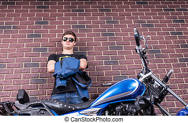 Young Man Holding his Jacket Behind his Motorbike