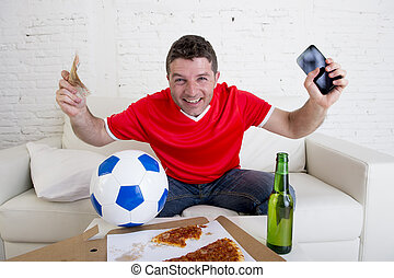young man holding mobile phone and money in his hands watching fottball game on television internet gambling concept