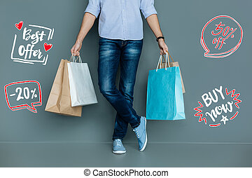 Young man holding paper bags after buying clothes on the sale