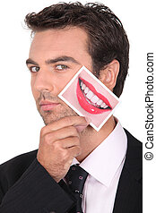 young man holding picture of feminine smiling mouth