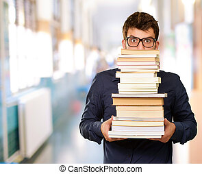 Young Man Holding Pile Of Books - Young Man Holding Pile Of...