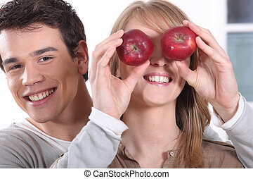 young man holding red apples before girfriend's eyes