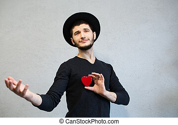 Young man holding red heart in hand.