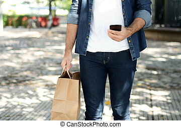 Young man holding shopping bag
