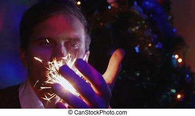 Young man holding sparkler sitting near a Christmas Tree