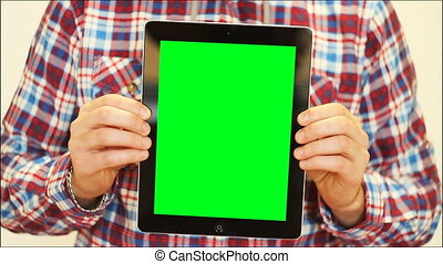 man holding tablet with green screen