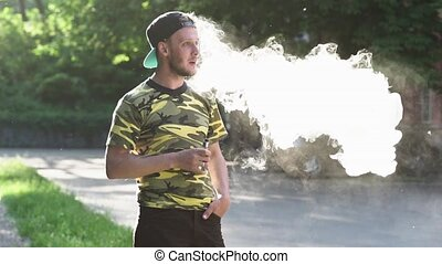 Young man holding vaping device - Young Man Holding Vaping...