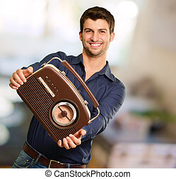 Young Man Holding Vintage Radio