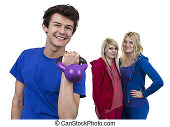 Young Man Holding Weight In Front Of Two Women