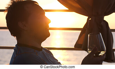 Young man holds a glass of white wine in a beach cafe at sunset near the sea.