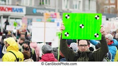 Young man holds poster with green screen on crowd background...