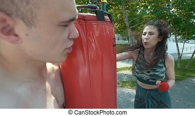 Young man holds punching bag to athletic woman engaged in boxing in the park at sunny day, slow-motion