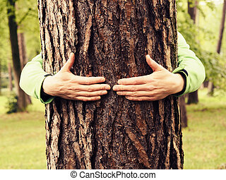 Young man hugs a tree