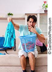 Young man husband ironing at home
