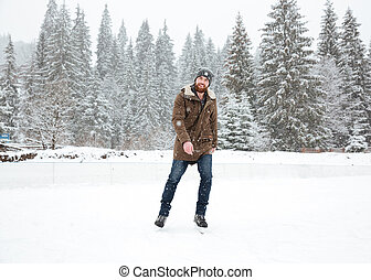Young man ice skating outdoors