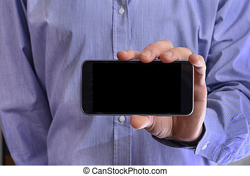 Young man in a blue shirt is holding a phone with the black scre
