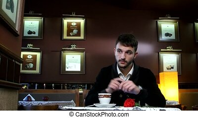 Young man in a cafe waiting for his girlfriend, phones her and leaves