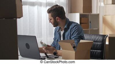 young man in a denim shirt checks the goods after delivery from the supplier. Man works with laptop and paper document. High quality 4k footage