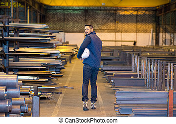 young man in a factory wearing protective workwear