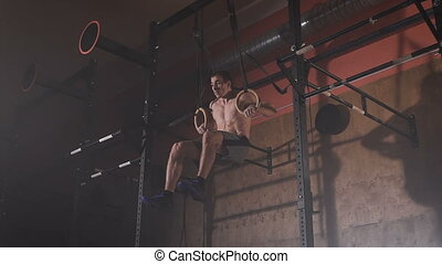 Young man in a good shape doing muscle-ups exercises on the sport rings at the gym.