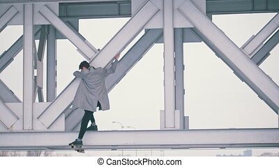Young man in a grey coat climb on the bridge span on a windy day