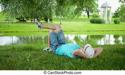 Young man in a hat is resting lying on the grass in a city park