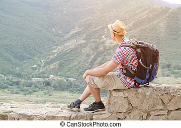 Young man in a hat with a backpack sits on a stone wall against a background of green mountains