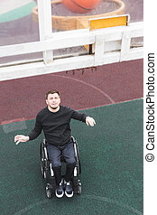 Young man in a wheelchair playing basketball.