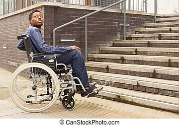 young man in a wheelchair waiting for help at the bottom of a staircase.