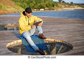 Young man in a yellow jacket and a black cap sitting on the dock with a tablet