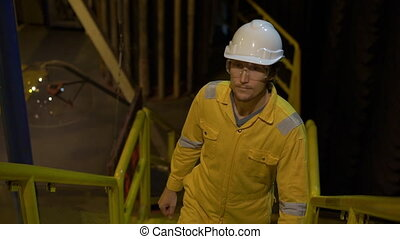 Young man in a yellow work uniform, glasses and helmet in industrial environment, oil Platform or liquefied gas plant. Slowmotion shot.