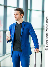 Young man in airport. Casual guy with luggage in international airport