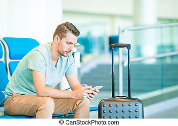 Young man in an airport lounge waiting for flight aircraft.