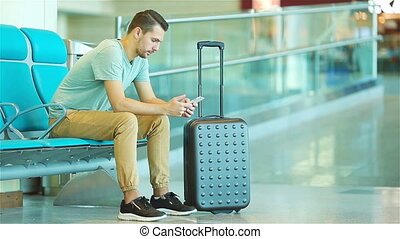 Young man in an airport lounge waiting for flight aircraft. Caucasian man with smartphone in the waiting room