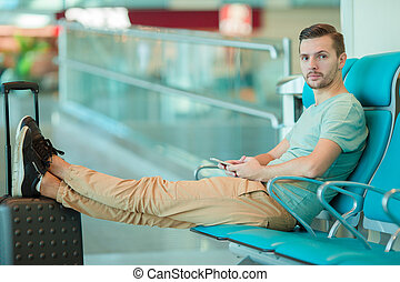 Young man in an airport lounge waiting for landing