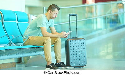 Young man in an airport lounge waiting for flight aircraft....